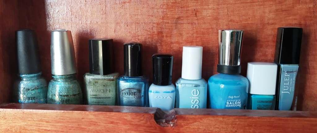 hilera de esmaltes azules de las marcas china glaze, avon, zoya, essie, sally hansen, julep y cover girl